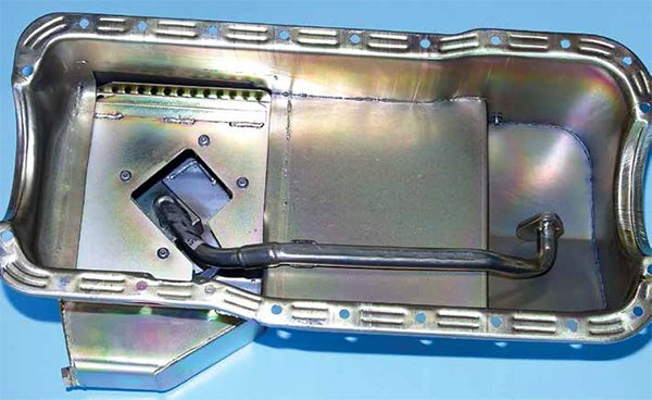The double-sump Fox-platform small-block oil pan is designed to clear the removable subframe and rack-and-pinion steering. The oil pump is located in the shallow sump with a pick-up tube to the deeper rear sump. This is a Fox road-race pan. The pick-up is attached at the pump and at the number-3 main cap. This is a challenging pick-up location for installing a pan.