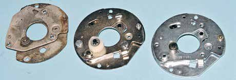 Shown here are three single-point breaker plates for the Autolite/Motorcraft distributor. On the far left is an original Autolite breaker plate with C-clip and steel pivot along with nylon sliders. In the middle is an aftermarket replacement breaker plate with a nylon/plastic pivot, which is prone to failure. On the right is a better-quality aftermarket breaker plate with a nylon/plastic spring-loaded pivot with improved durability.