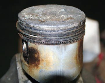 "From the side, this piston shows a buildup of sludge in and around the piston rings and ring lands, along with scuffing on the piston skirt, which is the shiny area. Both are indicative of excessive clearance that's caused from wear because of high mileage. In a running engine, this condition manifests itself through an internal noise referred to as ""piston slap."""