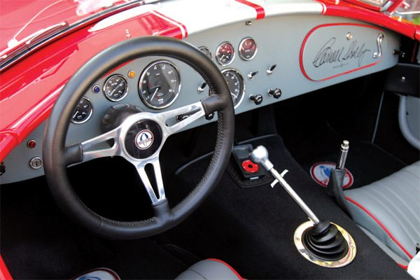 In a Superformance Cobra replica, as with the original Shelby Cobras from the 1960s, Smiths gauges fill the dash. A glovebox is also standard issue, just as it was back in the day. This car's owner had Carroll Shelby autograph the glovebox door. The leather wrapped steering wheel was ordered from Superformance as an option, since the standard wheels from Superformance are wood rimmed, as they were originally.