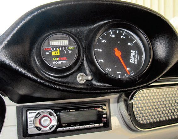 The importance of having the tach readily visible is also demonstrated in this Shelby gauge pod for 1965/1966 models. The older-style LED air/fuel gauge is a relatively coarse indicator and thus was put here as well. In this instance it is being used solely to verify both oxygen sensors are sufficiently active and responsive. This is done by using the toggle switch to go from reading the left bank to the right bank. A more-precise digital and LED air/fuel gauge is mounted on the dash to provide a more-exact, averaged air/fuel ratio as determined from its sampling location in the junction of the X-pipe.