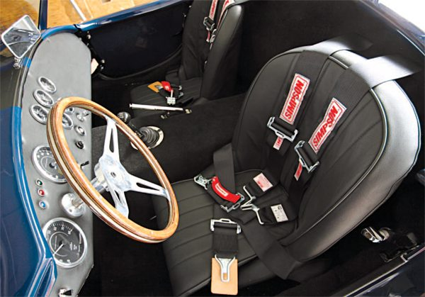 With four exceptions, our cockpit comes standard in the Factory Five Racing Mk4 Roadster Complete Kit. The leather seats are custom as is the steering wheel bezel, which we modified from an aluminum alternator pulley wheel. The gearshift lever was obtained from Modern Driveline. It's a Hurst 7-inch straight lever that we shortened by 2 inches, so we wouldn't run into the dashboard with it. As mentioned previously, the Lokar chrome emergency brake handle and system is also a much-needed modification.