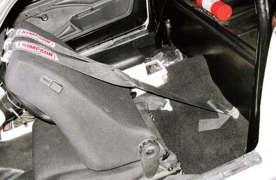 Some vehicles may not lend themselves to the installation of a roll bar or you may simply not want one. In these cases, you can still use shoulder belts but you have to find another location to securely mount them. This is a floor-mount location using eye bolts, locknuts, and mounting plates specially designed for this purpose. This required using a Y-style shoulder harness (one mounting point for both straps instead of one for each strap) and a less-than-optimal mounting point. Ideally, the shoulder straps should be parallel with the floorpan. This strap is mounted low and the angle of the strap is steep. This is not as safe or effective as the desired mounting method plus it is less likely to be accepted for racing.