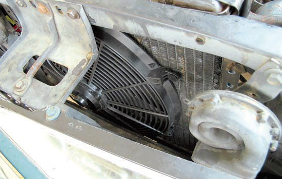 "The majority of engine-cooling fans are mounted between the radiator and the engine and thus ""pull"" air through the radiator core. ""Pusher"" fans mounted on the external side of the radiator can also be beneficial. When heat exchangers are mounted before the radiator they raise the temperature of the air reaching the radiator, reducing its cooling capability. Increasing the airflow rate can help offset this. The increased airflow from a pusher fan can improve the efficiency of the A/C condenser and/or auxiliary coolers because more air flows through them instead of some going around them."