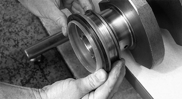 The desirable one-piece rear-main seal has been improved with a plastic installation sleeve, which prevents seal damage or distortion during installation. Mark dresses the crankshaft surface with assembly lube, then slips the seal onto the crank as shown. The plastic sleeve gets tossed.