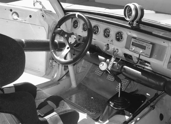 The sparse interior is all business. The driver is strapped to a Kirkey road-race aluminum seat and protected by a Safecraft fire system and 10-point roll cage. The Longacre Hot Lap timer on the dash keeps tabs of the on-track performance. (Photo Courtesy Rick Carlile)