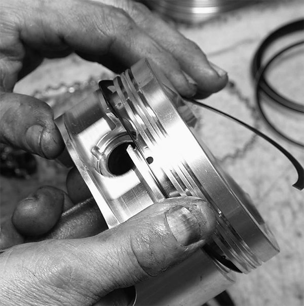 Pistons and rods have already been assembled. Because this is a 408ci stroker, the wrist pin is high in the piston, which calls for a support ring at the oil ring groove.