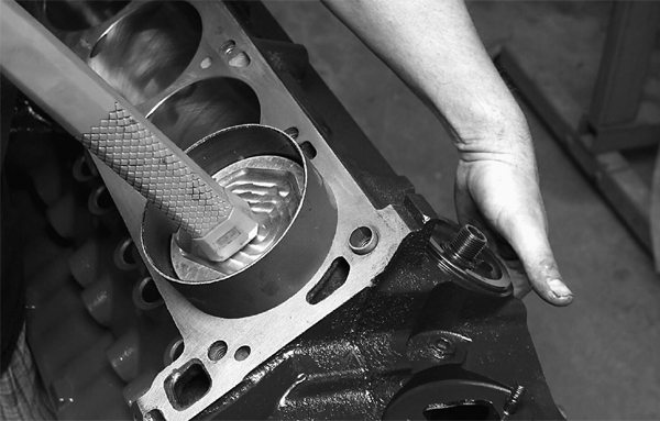 Speed-O-Motive uses billet piston ring compressors for ease of installation. The connecting rod's large end is carefully guided onto the rod journal.