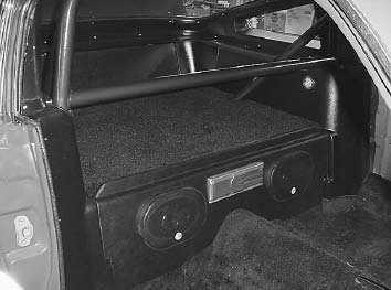 The rear seat in this Mustang was deemed useless when the roll cage was installed, so Don Rositch built a sturdy rear package shelf that also holds the speakers. It also has trim sticking up to keep items from sliding off the shelf. (Photo courtesy Mustang Don's)