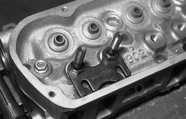 Pressed-in rocker arm studs should be replaced with screw-in studs with pushrod guide plates if you are going with factory heads.