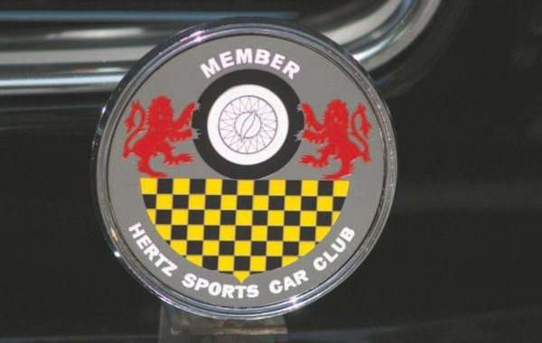 "The Hertz Sports Car Club was formed in 1958 to allow traveling business executives the opportunity to rent a fun vehicle while on an otherwise-boring business trip. The Club's logo featured lions, checkerboard, and a wire sports car wheel. The emblem was made into grille badges and given to renters who became members of the Club. Accompanying the badge were other ""goodies"" such as tote bags, garment bags, playing cards, and drinking glasses"