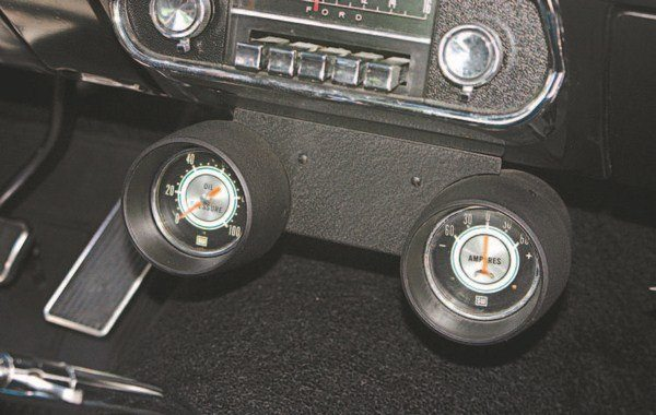 With no space in the dash cluster for the oil pressure gauge and ammeter, a pair of Stewart-Warner gauges was installed in a 1966 Mustang Rally-Pac housing that was suspended, upside down, under the radio.