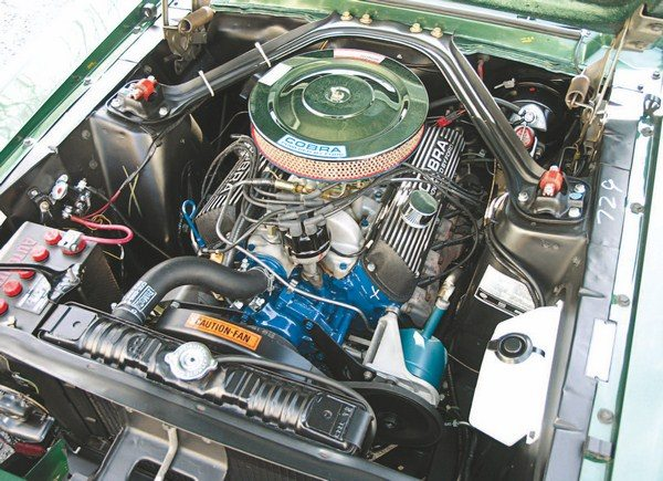 There were both similarities to and differences from the 1965 and 1966 GT350 under the hood of the new 1967 GT350. One similarity was the use of Ford's High Performance 289 with solid lifters, aluminum intake (with the same 715-cfm Holley as in the past two years), aluminum valve covers, and chrome air cleaner. Gone, however, were the cast-aluminum COBRA oil pan and welded steel tube headers, the 1967 Shelby relying instead on the same Ford-installed HiPo low-restriction exhaust manifolds that were replaced on the 1965 and 1966 Shelbys. Also deleted was the fender-to-fender Monte Carlo Bar. Somewhat alien to early Shelby owners were the power steering pump and power brake booster, both mandatory features of the new, more refined car.