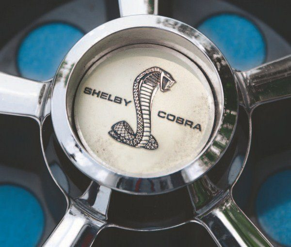 The same SHELBY COBRA graphic center cap decal was used on all 1967 wheels although different sizes were required because of the differing center-cap diameters. Unlike the badging on the cars' body, the wheel center cap decals did not specify GT350 or GT500, rather carrying SHELBY COBRA lettering. In the center of the wheel cover, the Thunderbird emblem was covered by a SHELBY COBRA decal.