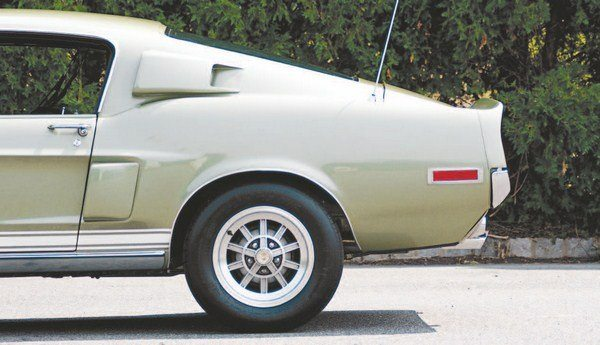 The nose and the rear taillight panel of the 1968 Shelby differed from those used on the 1967 cars, but seen in pure profile, the rears of the cars were identical. Tell-tales of the 1968 car (right) are the aluminum wheel lip molding, lower rocker panel trim, and the side marker lights. Mag-Star wheels, only available in 1967, are another clue to the model year. The rear-mounted antenna was a dealer relocation of the Mustang's fender-mounted antenna, done in an effort to alleviate radio static caused by poor ignition shielding from the all-fiberglass hood.