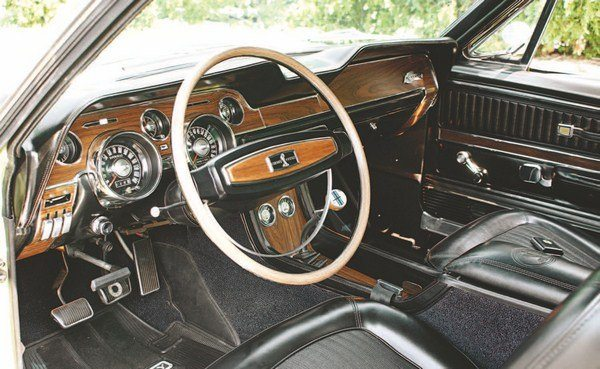 The dash layout of the 1968 Mustang was identical to that of the 1967 pony except that simulated woodgrain trim panels replaced the brushed aluminum finish parts of the previous car. Shelby interiors, therefore, mirrored this trend. Woodgrain seemed to convey more of a luxurious feel than did the former bare metal, and this was perfect for the more luxurious Shelby Mustangs. Shelby returned to the use of a simulated wood steering wheel and, for the first time, the cars got a floor console, which captured the front seat belts when not in use and contained additional engine gauges. By 1968, Shelby cockpits looked nothing like those of the first-year GT350s.