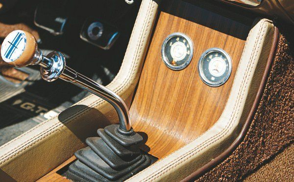 "For the first year ever, the Shelby Mustang received a betweenthe-seats floor console. Similar to the Mustang unit, the Shelby console replaces the sliding ""garage door"" storage compartment with an angled section that houses the ammeter and oil pressure gauges. Like in the 1967 Shelby, the 1968 dials are also furnished by Stewart-Warner. Mounted in the wood-grained floor console, they have a somewhat more integrated appearance than 1967's upside down Rally-Pac housing. Two pull knobs to the left of the console controlled the driving lights and (on convertibles) the power top."