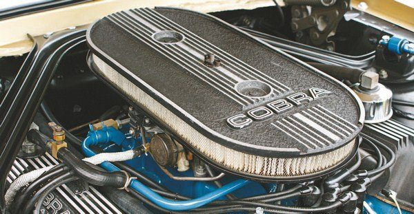 GT350s and GT500s used the 1967 GT500 aluminum air cleaner and lid (that was designed for a dual carb application to be secured with two wingnuts). Both the 1968 GT350 and GT500 used a single carburetor, and initially both had a bracket arrangement inside the air cleaner that featured two studs. This allowed the air cleaner lid to be secured with two wingnuts (left). Later cars deleted the bracket and simply drilled a hole in the center of the air cleaner top to be attached to the single carburetor's single stud (right). The unused attachment holes were plugged with press-in steel buttons.