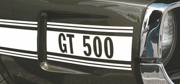 For the first time since the birth of the Shelby Mustang, the side stripes underwent major revisions. Gone was the traditional Microgramma Extended Bold lettering, this time replaced by a tall font (Franklin Gothic Demi Condensed), which allowed the GT350 (left) or GT500 (right) designation to fit within the nose brake intake ducts. The stripes gained additional colors, done in gold, white, black, or blue reflective tape (keyed to the car's body color). The lettering was cut out so that the designation showed through in the car's body color. Like the hood intakes and outlets, the semi-functional nose brake ducts had mesh inserts.
