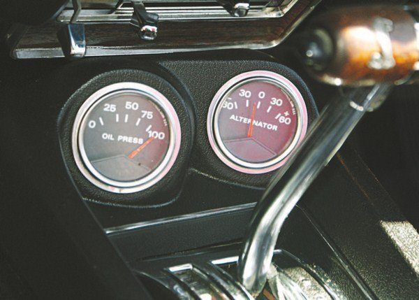 The center console contained provision for an ammeter and oil pressure gage at the front end, under the instrument panel center stack (left). The console was a two-part assembly a base, and an upper face. The Shelby console utilized a redesigned upper face, but the base was the same as the Mustang console. The gauge location was basically the same as for the 1967 and 1968 Shelbys but unlike in previous years, they were angled toward the driver (right). The gauges were manufactured by Faria in Connecticut (the same manufacturer of the 1966 tachometers).