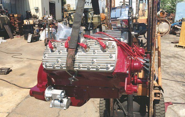 The engine is lifted by the two center exhaust header bolts; it is well balanced at these locations. When lowering the engine into your car, be extremely careful not to damage either the engine or the car. This engine belongs to Theresa Spurlock.