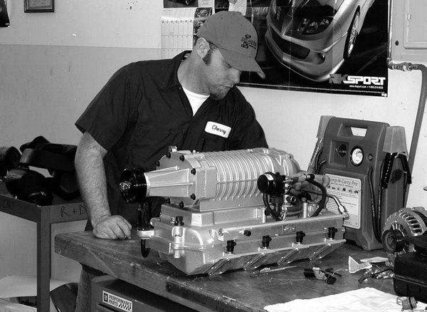 "Magnuson Products Inc. is world renown for building what many refer to as ""an Eaton with an attitude."" In this photo, a Magnuson technician is photographed running a volt check on either a Gen IV or Gen V Eaton/Magnuson bypass actuator solenoid to ensure that the unit is fail-safe."
