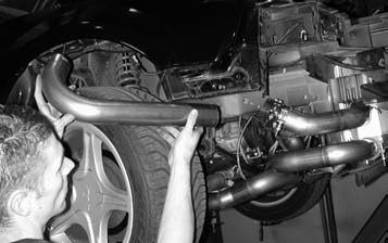 35. The J-bend intercooler pipe sweeps up around the inside fender well and through the opening inside the engine compartment, sliding one end into the 21⁄2-inch silicone hose using a T-bolt clamp to keep everything in place.