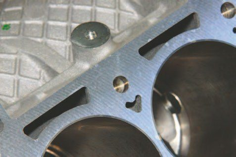 A close-up look illustrates the Coyote's paper-thin iron cylinder walls. Believe it or not, these cylinder sleeves can withstand 600 to 800 hp. Although some have gone to 1,000 hp without consequence, it is strongly suggested that you opt for thicker cylinder sleeves if you're going beyond 800 hp. Note the abundance of cooling passages between block and heads. In addition, 11-mm head bolts reach deep into the bottom of this block, which prevents deck distortion. Some engine builders have concluded that you don't need torque plates for honing with this block. It is still suggested, however, that you use a torque plate for cylinder honing.