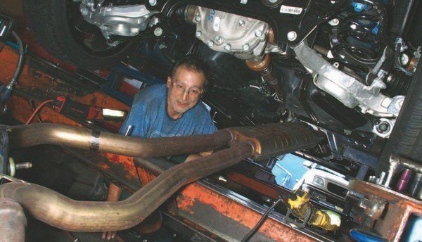 It takes two people to remove the S550 Mustang's dual exhaust system because it is all one huge assembly from the resonator amidships to the mufflers in back. Much of the weight can be credited to the resonator, which is very heavy.