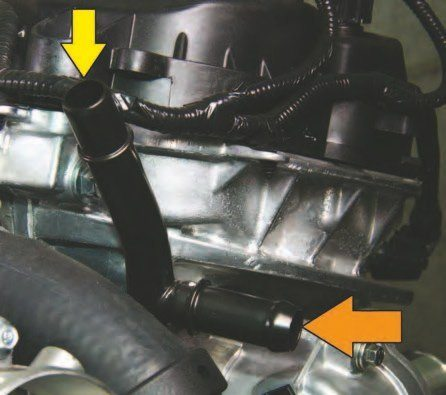 "Heater hosepipe connections are incorporated into the cylinder heads in front as shown here. This is the left-hand (driver) side with the cockeyed ""Y""-pipe. The top pipe at 12 o'clock (yellow arrow) is coolant flow from the heater hose. The lower pipe (orange arrow) is from the coolant expansion tank at the radiator. When you add coolant, it flows from the tank to this inlet pipe."